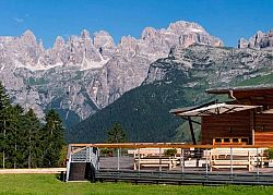 The sun terrace of the Dosson hut with a view on the Dolomites